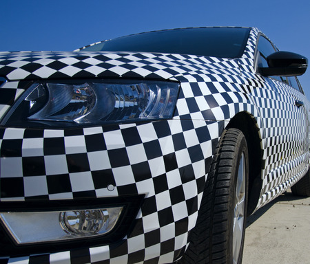 Closeup view of the car checkerboard pattern with detail headlight and rearview mirror with blue sky Stock Photo