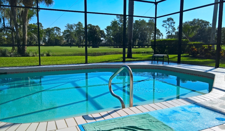 A view of the swimming pool in a house in Florida in the middle of Naples golf course with grass and palm trees under a blue sky on a sunny day Redactioneel