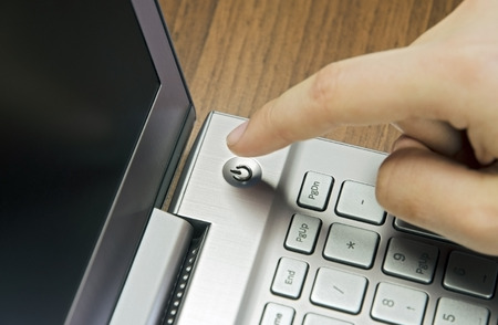 Closeup view of a hand with a finger, press the power button on metallic silver laptop keyboard, lying on a wooden mat blur