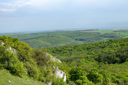 wine road: View of the hilly landscape of Palava with forests, rocks in South Moravia under a blue sky with clouds