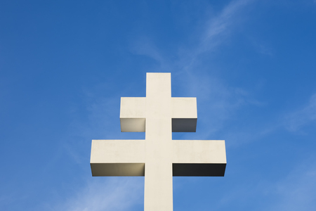 Photo of a large white double cross on a blue sky with white clouds Stock Photo
