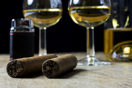Cuban cigars, bottle and two glass of whiskey and lighter, on old wooden board, with blurred background Stock Photo