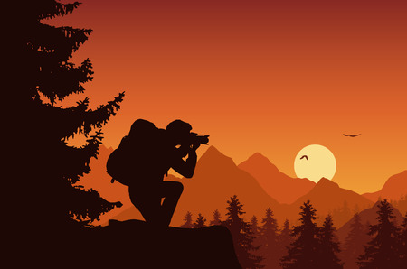 Mountain landscape with forest and tourist photographing flying birds on an orange sky with rising sun