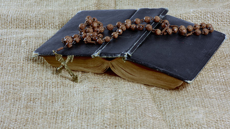 An open old book with a rosary in a hard cover lying on the jute