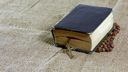 A closed old book with a rosary in a hard cover lying on a jute Stock Photo