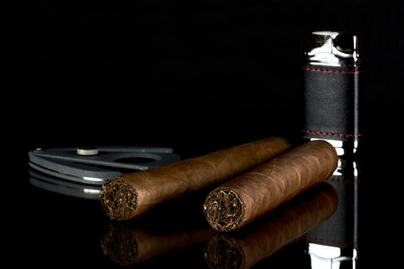 Two Cuban cigars with a lighter and a cutter on a glass mat with a black background Stock Photo