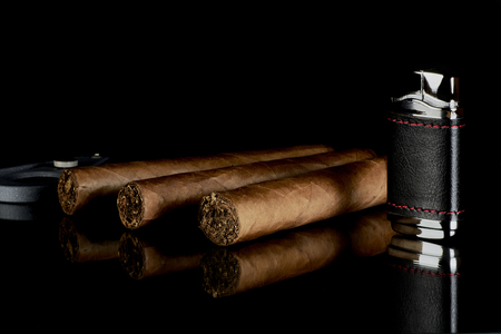 Cigar with cutter and lighter, reflected on a glass table on a black background