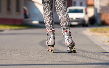 Female legs with inline roller skates. Asphalt road in the city with cars and buildings.