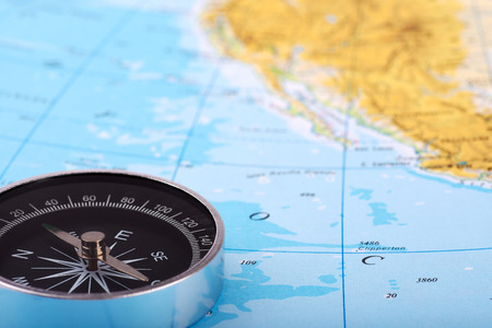 Photograph of a compass and a map of the atlas, with the ocean or the sea. Blurred background. 写真素材