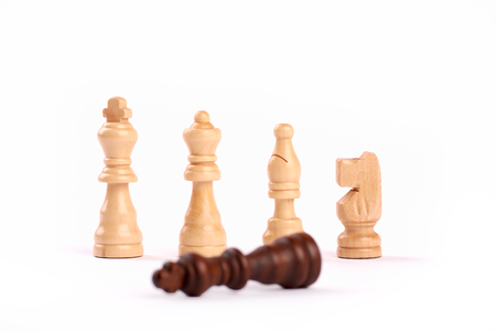 Row of white wooden chess pieces. Teamwork and cooperation, loser black king - Isolated on white background.
