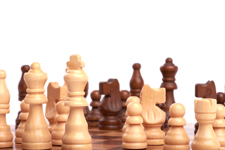 Playing a chess game or a battle. White and black wooden pieces on the board and planning a common team strategy - Isolated on white background. Banque d'images - 125369180
