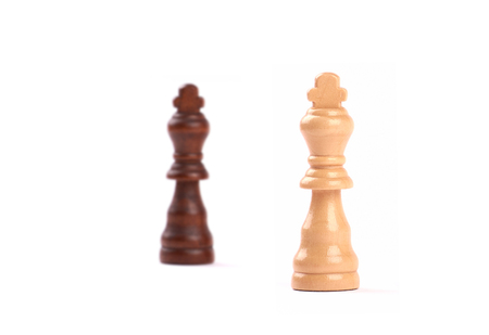 Two chess pieces. Black and white king of wood with blurred background. Isolated on white. Banque d'images - 125369181
