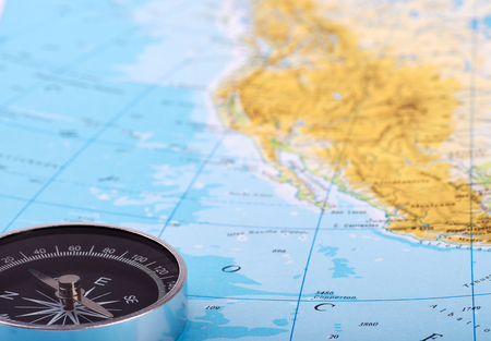Detailed view of a magnetic compass laid on a map or atlas with sea or ocean. Suitable for travel or vacation. Banque d'images - 125369184