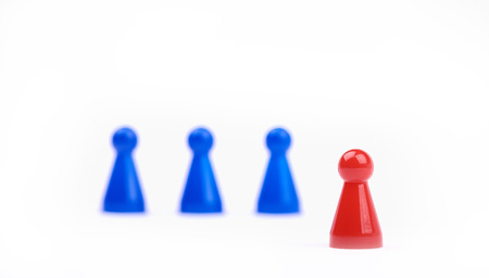 Three blurred blue game pieces as a team and one red sharpened figure as a leader in the foreground. Closeup photo with selective focus isolated on white background Banque d'images - 125369189