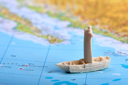 Plastic toy - ship or boat floating on a map or atlas with sea, ocean and land. Suitable as advertising for travel or vacation. Banque d'images - 125369218