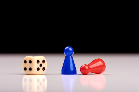 Standing blue playing figurine as winner and lying red figurine as loser with playing dice on white table top with black background. Space for your text. Banque d'images - 125369224