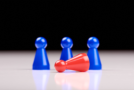 Standing three blue game pieces as winner and lying red figurine as loser on white table top with black background. Space for your text. Banque d'images - 125369226