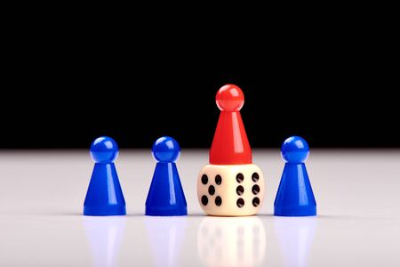 Three blue game pieces and between them one red piece stands on a dice as a winner or leader. Blurred black and white background Banque d'images - 125369222
