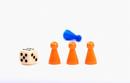 Three orange game pieces with a dice and a blue figure lying behind them. Isolated on white background. Banque d'images - 125369220