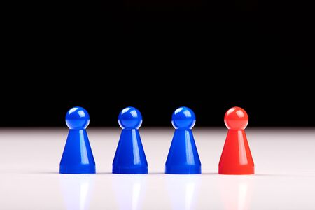 Three blue game pieces and a red figure standing next to them as a leader, boss or different. Blurred black and white background. Banque d'images - 125369225