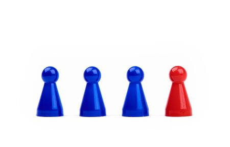Three plastic blue game pieces as a team and next to them a red piece as leader or different. Isolated on white background. Banque d'images - 125369229