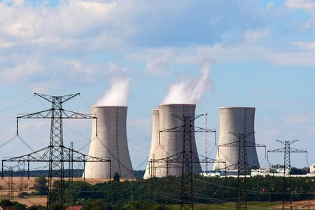 View of smoking chimneys of nuclear power plant, power lines and forest, under blue sky with white clouds Banque d'images - 127503772