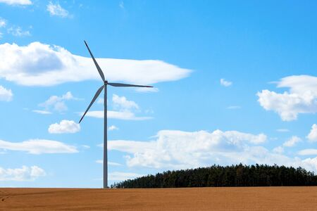Wind power station with one pole and windmill, near forest and cornfield in countryside under blue sky with white clouds.