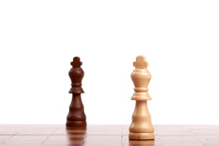 Two wooden chess pieces, black and white king on the board. Strategy and victory isolated on white background. Banque d'images - 127503784