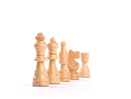 Row of white wooden chess pieces with selective focus isolated on white background. Banque d'images - 127504482