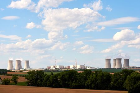 View of the smoking chimneys of a nuclear power plant in the landscape with trees, fields and houses under blue sky with clouds.