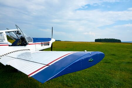 View of  aerobatic sport plane standing at airport. Grass and blue sky with clouds.