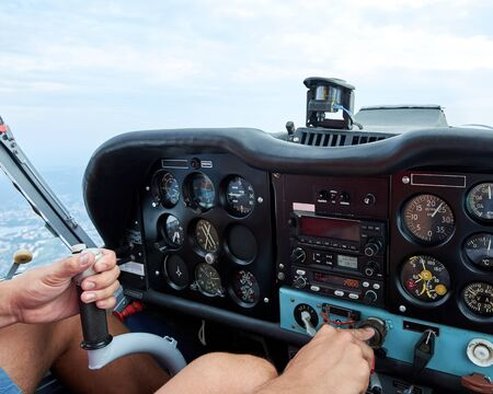 Cockpit view of a sports plane. Amateur pilot holding a hand control and throttle lever.