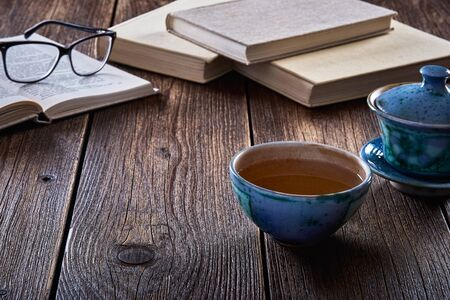Still life with old wooden table, mug or cup of tea and books. Фото со стока
