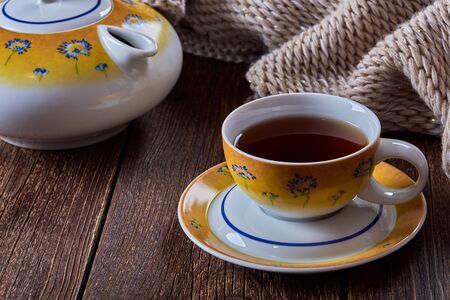 Still life with cup of tea and teapot. Knitted scarf or sweater on old wooden table. Фото со стока
