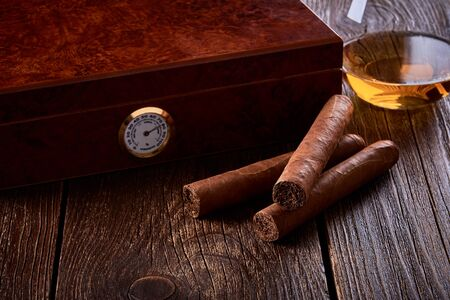 Still life with wooden box for humidification, three cigars and glass of whiskey on old table.