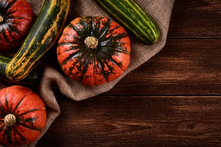Flat lay Photo Orange pumpkins and green zucchini on sacks of jute. Old wooden table top or background.