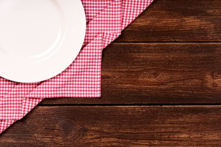 Flat lay of old wooden background with red checkered dishcloth, round white plate and space for text. Фото со стока