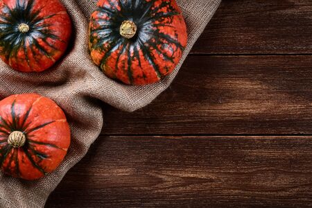 Flat lay view of three pumpkins on jute bag. Old wooden background or table top with space for text.