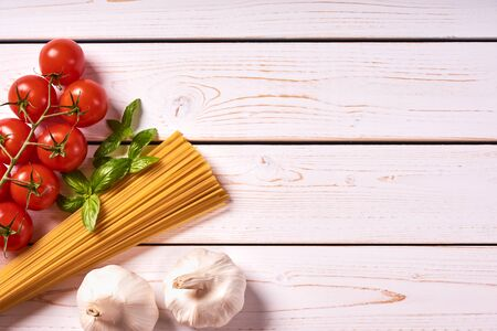 Flat lay view of pasta or spaghetti with bunch of tomatoes, garlic and basil leaves. Old white wooden background or table top with space for text.