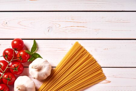 Flat lay view of white wooden table top with italian pasta or spaghetti, tomato and garlic. Green basil leaf as side dish.