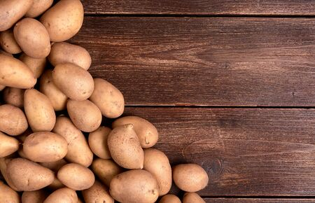 Harvested pile of potatoes on old wooden board table. Food or vegetables for cooking with space for text.