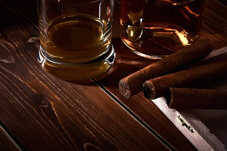 Still life with glass and bottle of alcohol, whiskey or brandy or rum. Three cuban cigars in a wooden box with space for text. Фото со стока