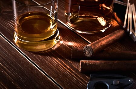Still life with glass and bottle of alcohol, whiskey or brandy or rum. Three cuban cigars, cutter and matches on old wooden table top with space for text.