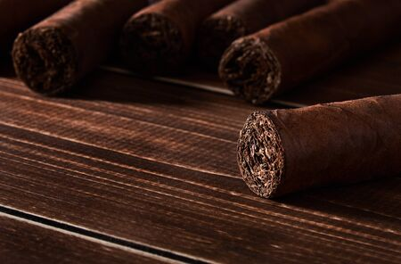 Still life with cuban cigar on old wooden board table with space for text and blurred background.