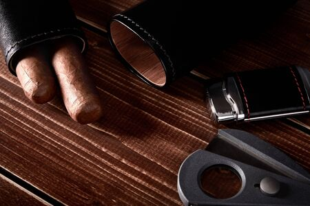 Still life with cuban cigars in black leather case, cutter and lighter on old wooden table top with space for text