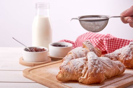 Still life with sugared Croissant, porcelain bowls with fruit jam and glass of milk and female hand with sugar, on white wooden table top with space for text Фото со стока