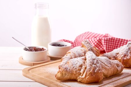 Still life on old wooden board table with three sweet croissants and fruit jam. Glass of milk on white background. Фото со стока