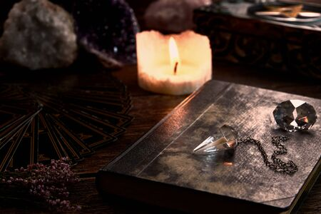 Still life with burning candle on old wooden table top, black fortune teller card, magic book and pentagram box and crystal pendulum. Suitable for magic or esoteric.