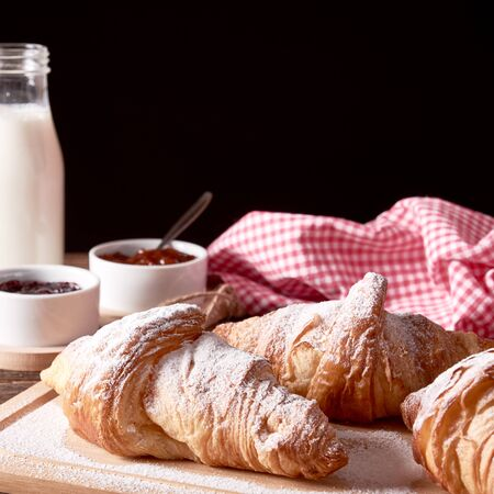 still life with french sugared croissants, glass of milk and bowl of jam on old wooden board and black background. Space for your text.