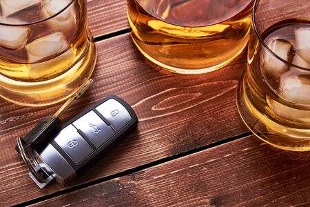 Modern car keys on wooden table top in bar. Glass and bottle of whiskey or other alcohol with ice. Suitable for the article on drunk driving.